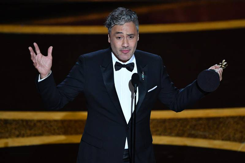 """(FILES) In this file photo New Zealand director/actor Taika Waititi accepts the award for Best Adapted Screenplay for """"Jojo Rabbit"""" during the 92nd Oscars at the Dolby Theatre in Hollywood, California on February 9, 2020. New Zealand filmmaker Taika Waititi will write and direct a new """"Star Wars"""" film, Disney announced May 4, 2020. Waititi has shot from indie acclaim to mainstream Hollywood success in recent years, overseeing Marvel superhero smash hit """"Thor: Ragnarok"""" in 2017 before winning a screenplay Oscar for Nazi satire """"Jojo Rabbit"""" in February.  / AFP / Mark RALSTON"""