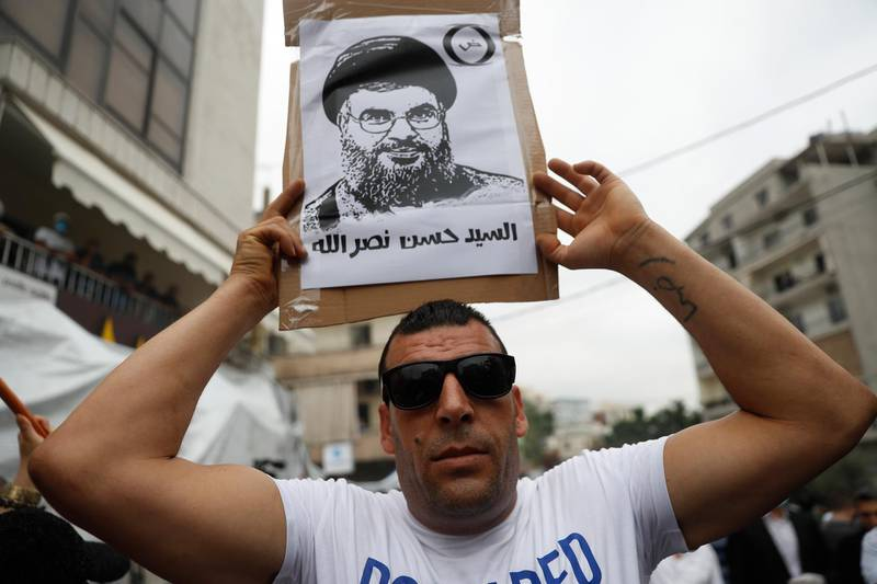 """A Hezbollah supporter holds a placard depicting its leader Sayyed Hassan Nasrallah, during a protest against U.S. interference in Lebanon's affairs, near the U.S. embassy, in Aukar northeast of Beirut, Lebanon, Friday, July 10, 2020. The Arabic words on the placard read:""""Sayyed Hassan Nasrallah."""" (AP Photo/Hussein Malla)"""