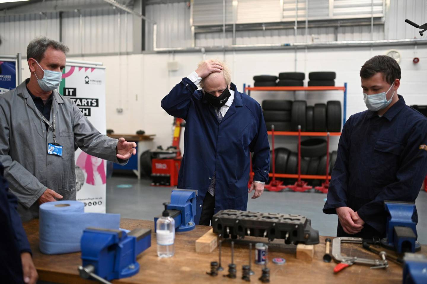 Britain's Prime Minister Boris Johnson (C) gestures in the automotive shop during a visit to Kirklees College Springfield Sixth Form Centre in Dewsbury, West Yorkshire, Britain June 18, 2021. Oli Scarff/Pool via REUTERS