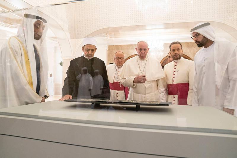 ABU DHABI, UNITED ARAB EMIRATES - February 4, 2019: Day two of the UAE papal visit -  HH Sheikh Mohamed bin Zayed Al Nahyan, Crown Prince of Abu Dhabi and Deputy Supreme Commander of the UAE Armed Forces (L), His Eminence Dr Ahmad Al Tayyeb, Grand Imam of the Al Azhar Al Sharif (centre L), His Holiness Pope Francis, Head of the Catholic Church (centre R), and HE Mohamed Khalifa Al Mubarak, Chairman of the Department of Culture and Tourism and Abu Dhabi Executive Council Member (R), look at leaves from the Blue Qurían courtesy of Zayed National Museum, during a dinner reception at Al Mushrif Palace.  ( Ryan Carter / Ministry of Presidential Affairs ) ---
