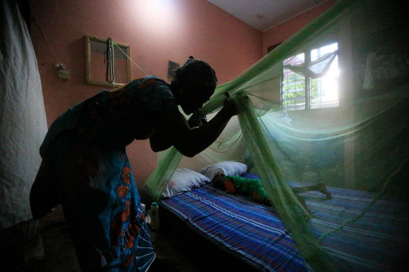 epaselect epa06689943 A woman installs a mosquito net over her child in Abidjan, Ivory Coast, 24 April 2018. World Malaria Day is observed on 25 April each year to recognize the global efforts to control Malaria, it was established in May 2007 by the World Health Organization (WHO).  EPA-EFE/LEGNAN KOULA