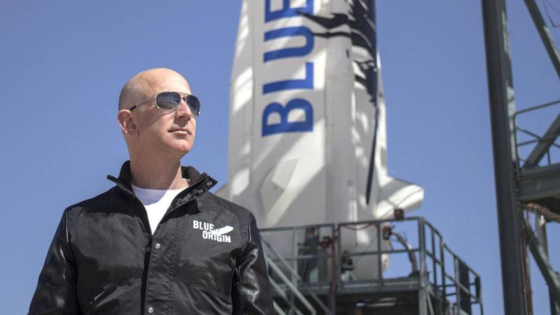 """This April 24, 2015 handout photograph obtained courtesy of Blue Origin shows Jeff Bezos, founder of Blue Origin, at New Shepard's West Texas launch facility before the rocket's maiden voyage. - The two companies leading the pack in the pursuit of space tourism say they are just months away from their first out-of-this-world passenger flights -- though neither has set a firm date. Virgin Galactic, founded by British billionaire Richard Branson, and Blue Origin, by Amazon creator Jeff Bezos, are racing to be the first to finish their tests -- with both companies using radically different technology. (Photo by HO / BLUE ORIGIN / AFP) / With AFP Story by Ivan COURONNE: First space tourist flights could come in 2019   == RESTRICTED TO EDITORIAL USE  / MANDATORY CREDIT:  """"AFP PHOTO /  BLUE ORIGIN"""" / NO MARKETING / NO ADVERTISING CAMPAIGNS /  DISTRIBUTED AS A SERVICE TO CLIENTS  =="""
