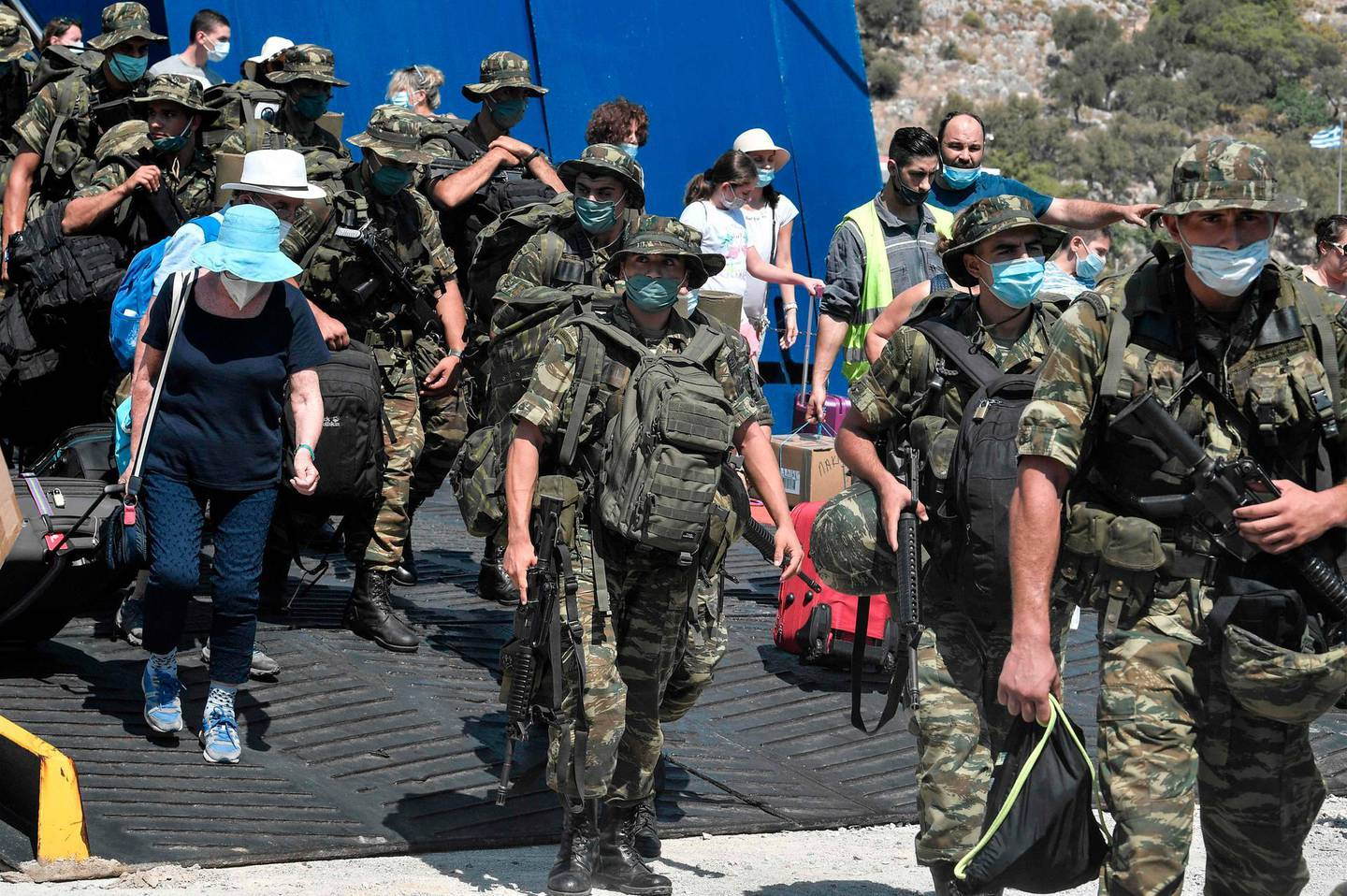 Greek soldiers and tourists deisembark from a ferry at the port of the tiny Greek island of Kastellorizo, officially Megisti, the most south-eastern inhabited Greek island in the Dodecanese, situated two kilometers off the south coast of Turkey.  / AFP / Louisa GOULIAMAKI