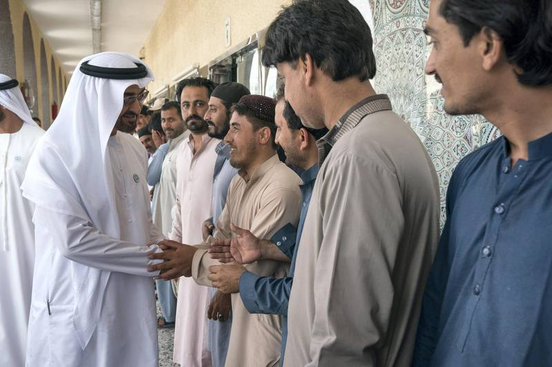 ABU DHABI, UNITED ARAB EMIRATES -  February 22, 2018: HH Sheikh Mohamed bin Zayed Al Nahyan, Crown Prince of Abu Dhabi and Deputy Supreme Commander of the UAE Armed Forces (L), greets staff at the carpet market in Mina Zayed Port area.  ( Ryan Carter for the Crown Prince Court - Abu Dhabi ) ---