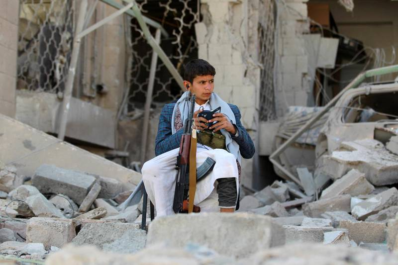 An armed Yemeni youth, loyal to the Shiite Muslim Huthi movement that controls Sanaa, sits amid the rubble on December 5, 2014, guarding the damaged house of the Iranian ambassador in the Yemeni capital which was targeted by a car bomb earlier this week. Al-Qaeda's local branch said on December 3  it was behind a car bombing that killed one person and wounded 17 outside the residence of Iran's ambassador the Yemeni capital, where Tehran is accused of backing Shiite militia.  AFP PHOTO / MOHAMMED HUWAIS (Photo by MOHAMMED HUWAIS / AFP)