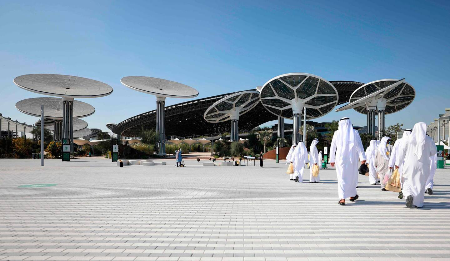 People walk towards the Sustainability Pavilion, a week ahead of its public opening, at the Dubai Expo 2020 in Dubai on January 16, 2021. The six-month world fair, a milestone for the emirate which has splashed out $8.2 billion on the eye-popping venue in the hope of boosting its soft power and resetting the economy, will now open its doors in October 2021. / AFP / Karim SAHIB