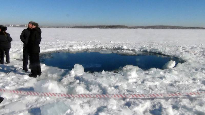 """A handout photo taken on February 15, 2013, and provided by Chelyabinsk region police department shows people standing near a six-metre (20-foot) hole in the ice of a frozen lake, reportedly the site of a meteor fall, outside the town of Chebakul in the Chelyabinsk region. A plunging meteor exploded today with a blinding flash above central Russia, setting off a shock wave that shattered windows and hurt over 500 people in an event unprecedented in modern times. The office of the local governor said in a statement that a meteorite had fallen into a lake outside the town of Chebakul in the Chelyabinsk region. AFP PHOTO / CHELYABINSK REGION POLICE DEPARTMENT -- RESTRICTED TO EDITORIAL USE - MANDATORY CREDIT """"AFP PHOTO /  CHELYABINSK REGION POLICE DEPARTMENT"""" - NO MARKETING NO ADVERTISING CAMPAIGNS - DISTRIBUTED AS A SERVICE TO CLIENTS -- (Photo by - / CHELYABINSK REGION POLICE DEPART / AFP)"""