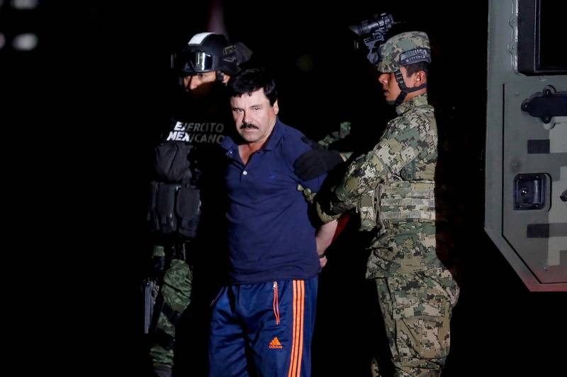 """FILE PHOTO: Joaquin """"El Chapo"""" Guzman is escorted by soldiers during a presentation in Mexico City, Jan. 8, 2016. REUTERS/Tomas Bravo/File Photo/File Photo"""