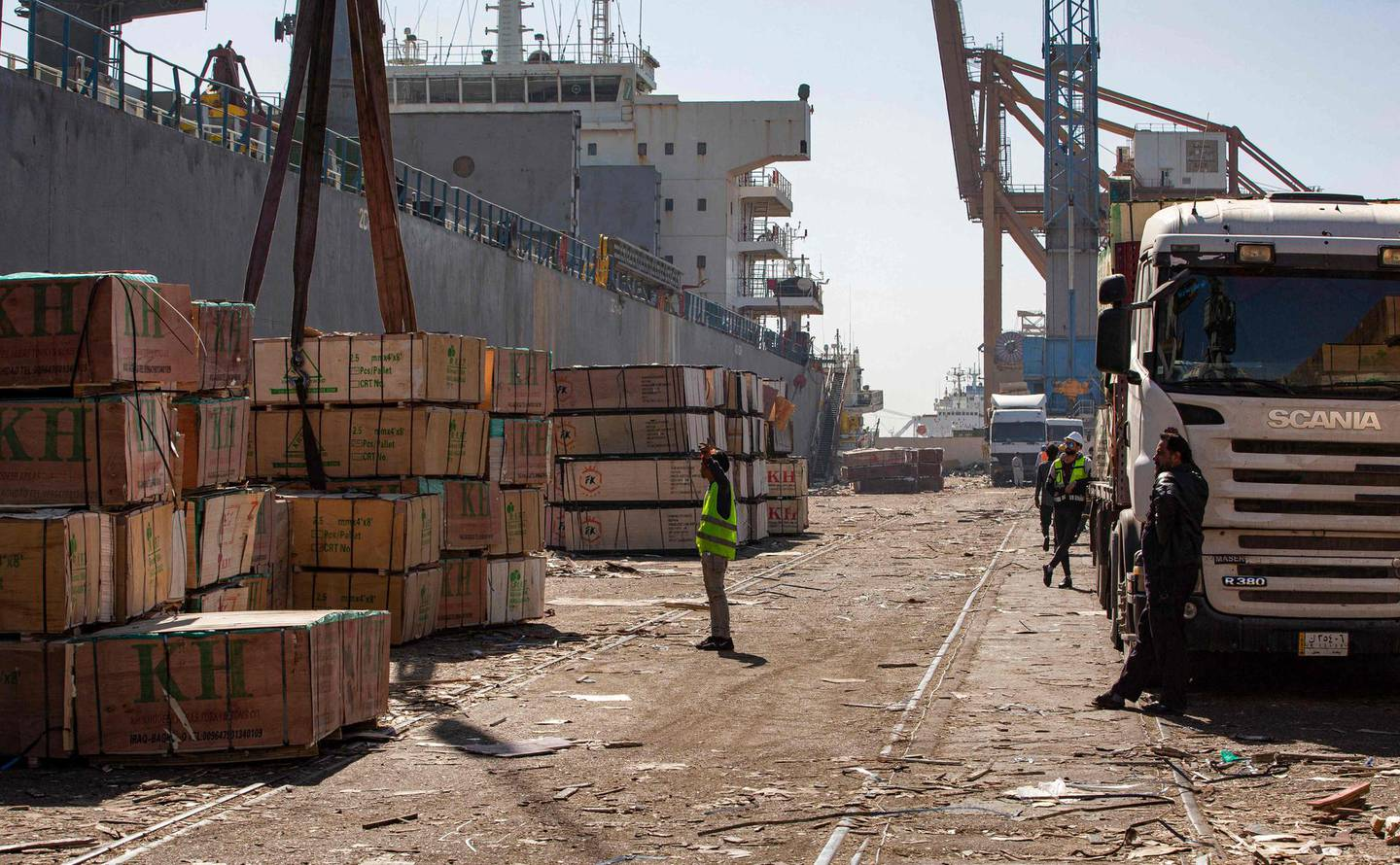 This picture taken on March 14, 2021 shows pallets of imported wood being unloaded off a cargo ship on the pier at the port of Umm Qasr, south of Iraq's southern city of Basra. Iraq is ranked the 21st most corrupt country by Transparency International. In January, the advocacy group said public corruption had deprived Iraqis of basic rights and services, including water, health care, electricity and jobs. It said systemic graft was eating away at Iraqis' hopes for the future, pushing growing numbers to try to emigrate. In 2019, hundreds of thousands of protesters flooded Iraqi cities, first railing against poor public services, then explicitly accusing politicians of plundering resources meant for the people. / AFP / Hussein FALEH