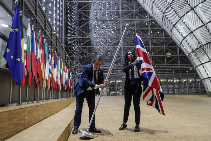 TOPSHOT - EU Council staff members remove the United Kingdom's flag from the European Council building in Brussels on Brexit Day, January 31, 2020. Britain leaves the European Union at 2300 GMT on January 31, 2020, 43 months after the country voted in a June 2016 referendum to leave the block. The withdrawal from the union ends more than four decades of economic, political and legal integration with its closest neighbours. / AFP / POOL / OLIVIER HOSLET