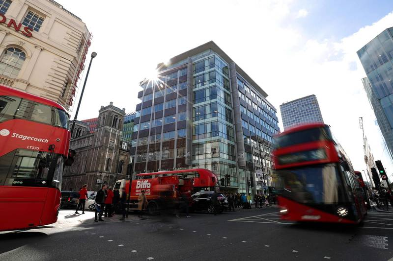(FILES) In this file photo taken on March 21, 2018 Traffic, including red London busses, passes the shared building which houses the offices of Cambridge Analytica in central London. A British judge on Friday, March 23, 2018 approved a warrant to search the London offices of Cambridge Analytica, the scandal-hit communications firm at the heart of the Facebook data privacy storm. / AFP PHOTO / Daniel LEAL-OLIVAS