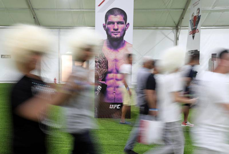 Abu Dhabi, United Arab Emirates - September 06, 2019: Fight fans walk passed a poster of Khabib Nurmagomedovat at the UFC fan zone. Friday the 6th of September 2019. Yes Island, Abu Dhabi. Chris Whiteoak / The National