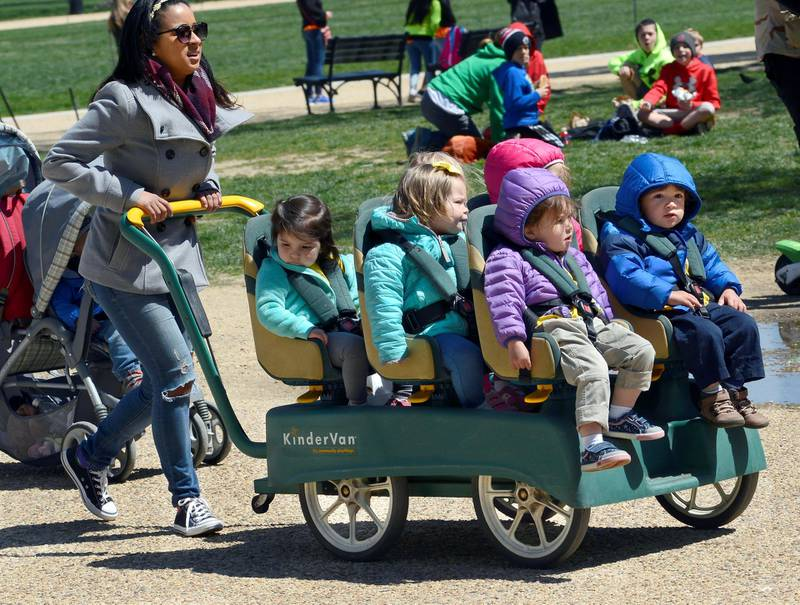 WASHINGTON, D.C. - APRIL 20, 2018:  A daycare center employee pushes a KinderVan filled with preschool children on an outing along the National Mall in Washington, D.C. (Photo by Robert Alexander/Getty Images)
