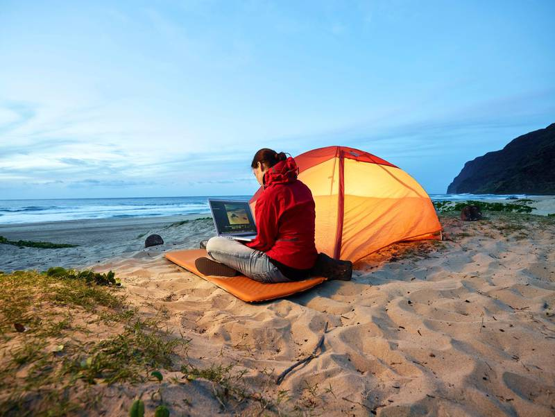 USA, Hawaii, Kauai, Polihale State Park, woman using laptop at tent on the beach at dusk, Getty Images