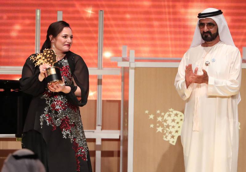 """British teacher Andria Zafirakou (L) receives the """"Global Teacher Prize"""" from Sheikh Mohammed bin Rashid al-Maktoum, Vice-President and Prime Minister of the UAE and Ruler of Dubai during an award ceremony in Dubai on March 18, 2018.   Zafirakou who  was among ten finalists chosen from 179 countries, won one million dollars of prize money. / AFP PHOTO / KARIM SAHIB"""