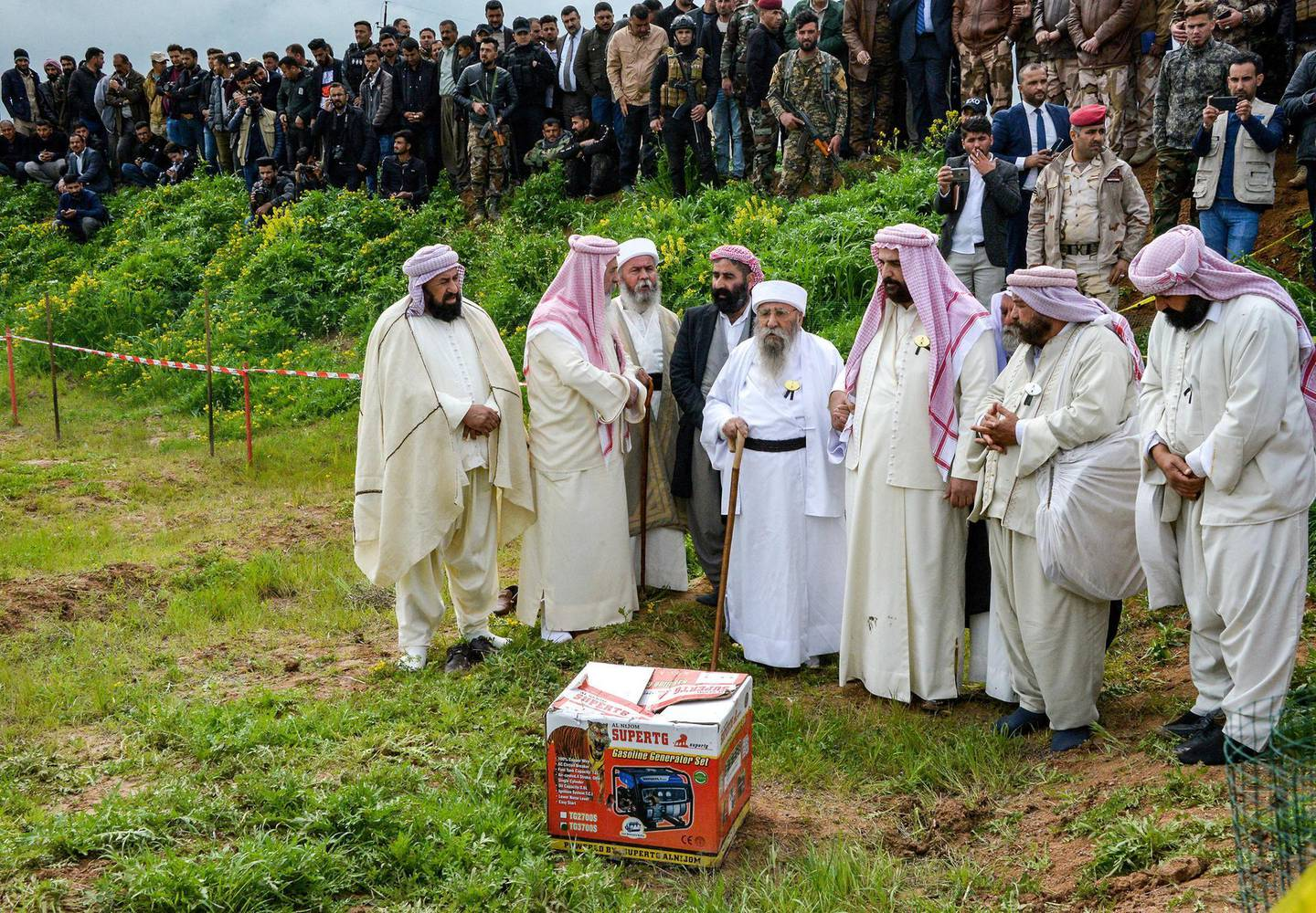 Iraqi Yazidi clerics attend the exhumation of a mass-grave of hundreds of Yazidis killed by Islamic State (IS) group militants in the northern Iraqi village of Kojo in Sinjar district on March 15, 2019. - Iraqi authorities exhumed the mass grave in an operation aiming to extract remains and identify victims of an August 2014 massacre of Yazidis by IS fighters as they entered the village of Kojo, during investigations of genocide against the decimated minority. (Photo by Zaid AL-OBEIDI / AFP)
