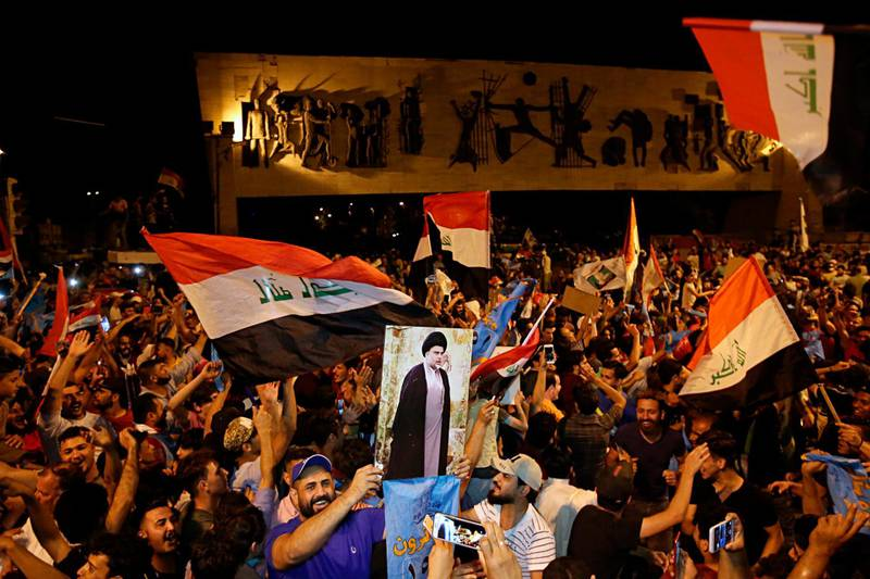 Followers of Shiite cleric Muqtada al-Sadr, displayed on the poster, celebrate in Tahrir Square, Baghdad, Iraq, early Monday, May 14, 2018. The political coalition of influential Shiite cleric Muqtada al-Sadr took an early lead in Iraq's national elections in partial returns announced late Sunday by the Iraqi electoral commission. (AP Photo/Karim Kadim)