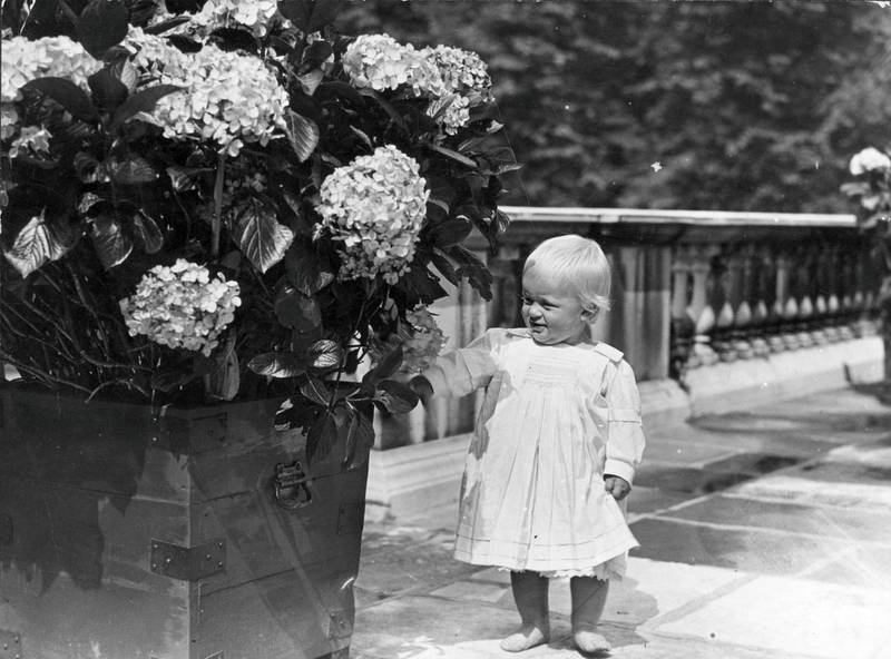 July 1922:  At one year old, Prince Philip of Greece shows an interest in things floral.  (Photo by Topical Press Agency/Getty Images)