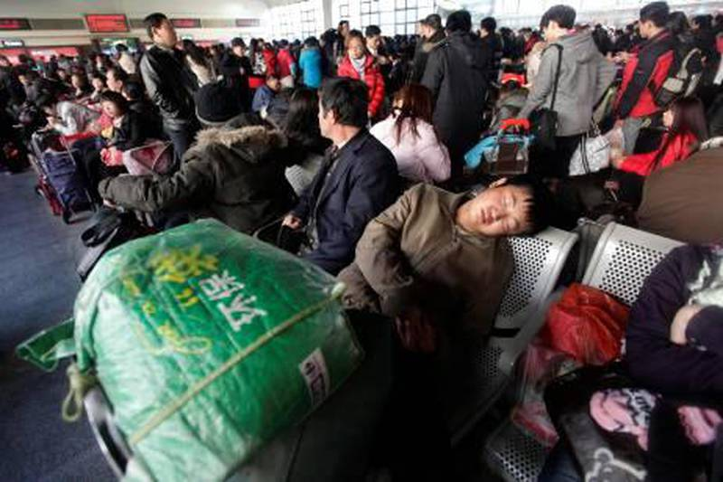 A passenger sleeps as he waits for his train at a waiting hall of the Beijing West Railway Station, January 26, 2011. January 19  marked the beginning of the annual Spring Festival travel rush, with an expected 2.56 billion passenger trips in the coming 40 days. REUTERS/Jason Lee (CHINA - Tags: TRANSPORT) *** Local Caption ***  PEK302_CHINA-_0126_11.JPG