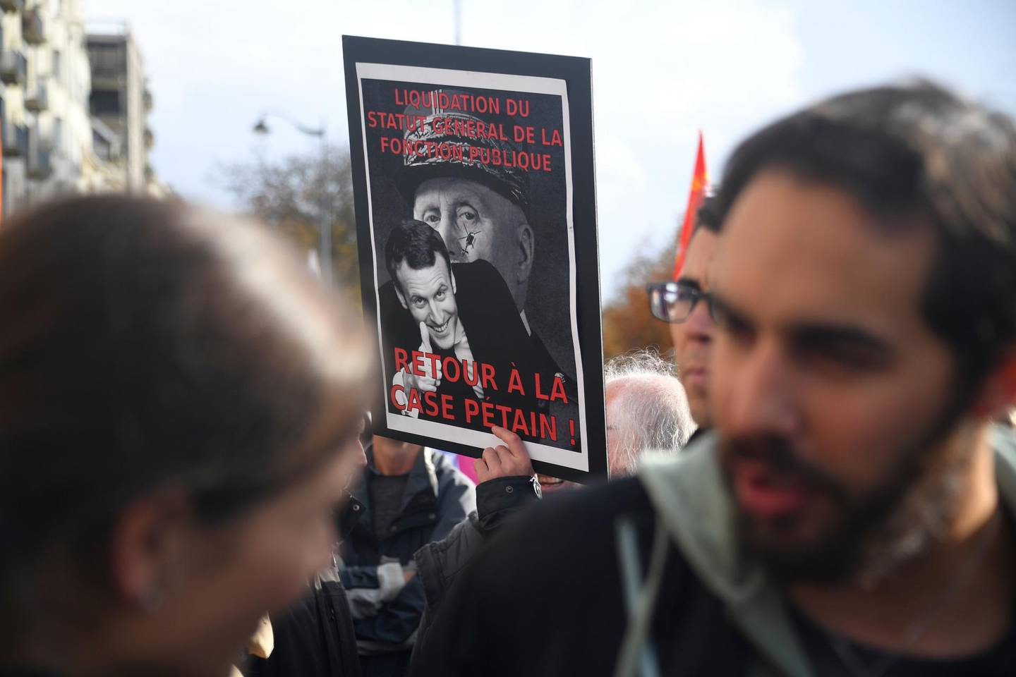 """A teacher holds a banner that reads, """"Liquidation of the general status of the civil service. Back to square Petain"""" during a nationwide strike to denounce the abolition of posts in the national education system in Rennes, westen France on November 12, 2018.  / AFP / DAMIEN MEYER"""