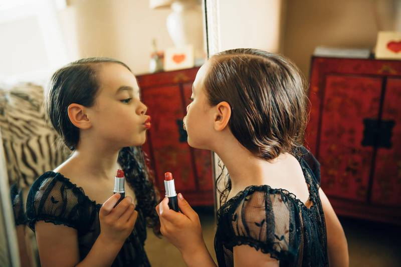 Mixed race girl applying lipstick in mirror. Getty Images