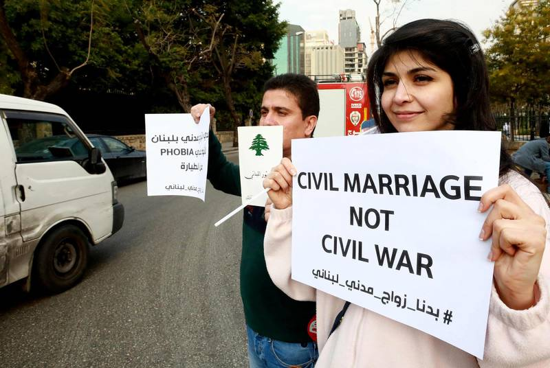 Lebanese demonstrators carry placards during a gathering against the ongoing ban on civil unions outside the Ministry of Interior in the capital Beirut on February 23, 2019.  / AFP / ANWAR AMRO