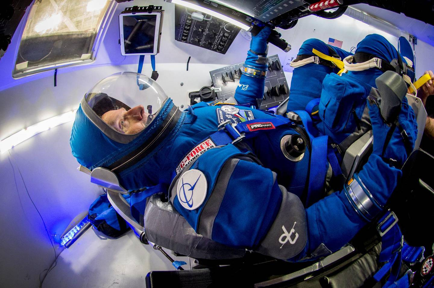 Chris Ferguson, Boeing director of crew and mission systems and a former astronaut, checks out the new, blue Starliner spacesuit in a mockup of the company's commercial crew spacecraft. Courtesy Boeing