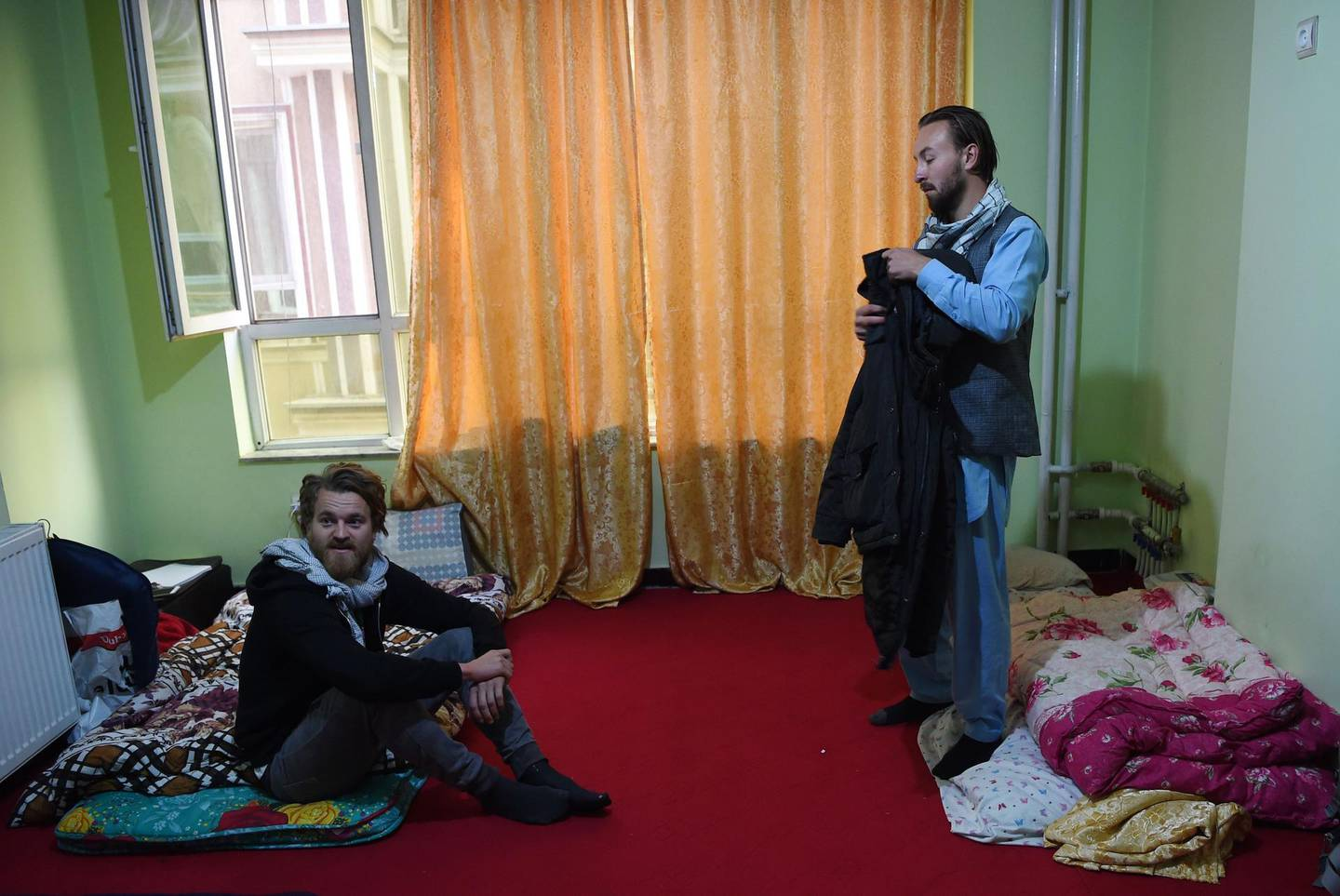 In this photo taken on November 11, 2018, Norwegian tourist Jorn Bjorn Augestad (L), 29, and Dutch tourist Ciaran Barr (R), 24, talk with Afghan Couchsurfing host Naser Majidi (unseen), 27, at a house in Kabul.  Once a popular stop on the well-worn hippy trail between Europe and South Asia in the 1970s, Afghanistan has seen the number of foreign travellers crossing its borders dwindle in the past four decades of almost non-stop conflict. But dozens still make the dangerous journey every year, ignoring clear warnings from their own governments to stay away from a country infested with suicide attackers, kidnappers and armed robbers, and which by some estimates is now the world's deadliest conflict zone.  - TO GO WITH AFP STORY AFGHANISTAN-LEISURE,FEATURE BY ALLISON JACKSON  / AFP / WAKIL KOHSAR / TO GO WITH AFP STORY AFGHANISTAN-LEISURE,FEATURE BY ALLISON JACKSON