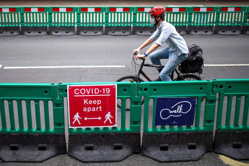 LONDON, UNITED KINGDOM - JUNE 12: A cyclist passes along Oxford Street where barriers have been installed to widen the pavement to enable social distancing on June 12, 2020 in London, England.  As the British government further relaxes Covid-19 lockdown measures in England, this week sees preparations being made to open non-essential stores and Transport for London handing out face masks to commuters. International travelers arriving in the UK will face a 14-day quarantine period. (Photo by Justin Setterfield/Getty Images)