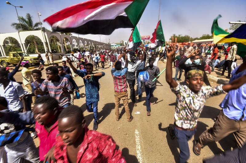 Sudanese demonstrators march with national flags as they gather during a rally demanding a civilian body to lead the transition to democracy, outside the army headquarters in the Sudanese capital Khartoum on April 13, 2019. - Sudan's new military leader General Awad Ibn Ouf resigned late on April 12 just a day after being sworn in, as the country's army rulers insisted they would pave the way for a civilian government. (Photo by AHMED MUSTAFA / AFP)