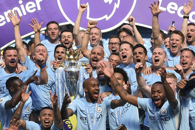Manchester City's Spanish manager Pep Guardiola (C) holds the Premier League trophy on the pitch with Manchester City players after the English Premier League football match between Manchester City and Huddersfield Town at the Etihad Stadium in Manchester, north west England, on May 6, 2018. (Photo by Oli SCARFF / AFP) / RESTRICTED TO EDITORIAL USE. No use with unauthorized audio, video, data, fixture lists, club/league logos or 'live' services. Online in-match use limited to 75 images, no video emulation. No use in betting, games or single club/league/player publications. /