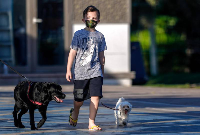 Abu Dhabi, United Arab Emirates, October  23, 2020.    A boy wearing a face mask takes his dogs on a stroll on the Corniche on a Friday morning.Victor Besa/The NationalSection:  NAfor:  Standalone/Weather