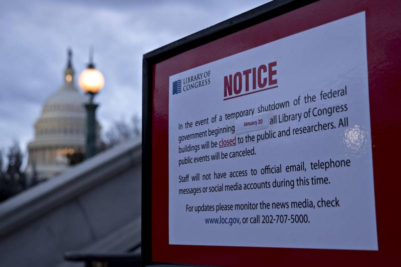 The U.S. Capitol stands past a temporary shutdown sign outside the Library of Congress in Washington, D.C., U.S., on Sunday, Jan. 21, 2018. The House and Senate are back in session Sunday with a federal government shutdown in its second day amid a spending-bill impasse in Congress. The House is supposed to be on recess this week, but members stayed in Washington as negotiations continue. Photographer: Andrew Harrer/Bloomberg