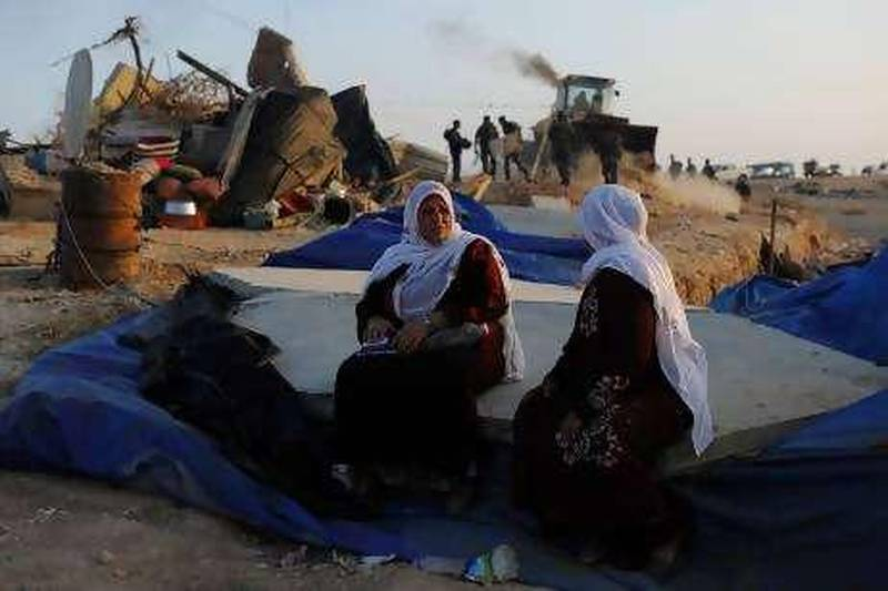 Bedouin women sit on rubble as Israeli policemen destroy the makeshift houses of the Al-Akarib bedouin village in the Israeli Negev desert on August 10, 2010, two weeks after the same houses built without permission were destroyed on July 27 and some 300 Bedouins were evicted. AFP PHOTO/DAVID BUIMOVITCH