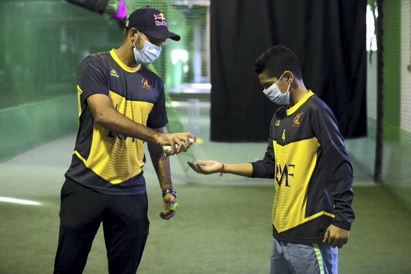 Dubai, United Arab Emirates - Reporter: N/A. News. Coronavirus/Covid-19. UAE player Chirag Suri sanitises a players hands at Front Foot Sports cricket academy in Al Quoz. Saturday, October 17th, 2020. Dubai. Chris Whiteoak / The National