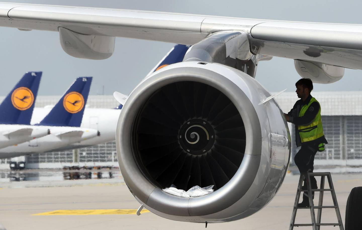 """(FILES) This file photo taken on April 28, 2020 shows a technician of the German airline Lufthansa working at a parked plane at the """"Franz-Josef-Strauss"""" airport in Munich, southern Germany.  German airline Lufthansa is to cut 22,000 jobs due to the effects of the coronavirus pandemic, a spokesman said on June 11, 2020. / AFP / Christof STACHE"""