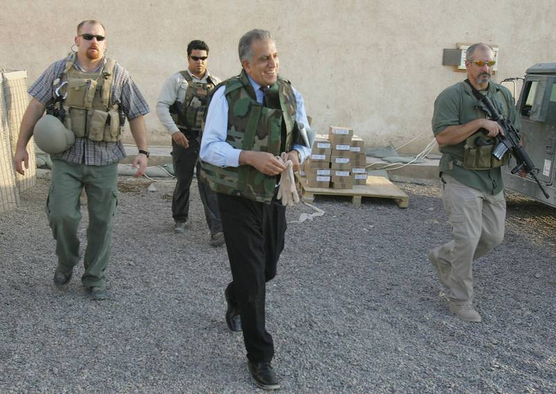 (FILES) In this file photo taken on October 15, 2005, US Ambassador to Iraq Zalmay Khalilzad, wearing a flack jacket and surrounded by bodyguards from the US security firm Blackwater, leaves the Civil and Military Operation Center (CMOC) in Fallujah. Iraqis on December 23, 2020 were outraged, heartbroken but not surprised to hear of a US presidential pardon for four American security guards convicted of killing Iraqi civilians in Baghdad in 2007. The Blackwater team, contracted to provide security for US diplomats in Iraq following the American-led invasion in 2003, claimed they were responding to insurgent fire. The bloody episode left at least 14 Iraqi civilians dead and 17 wounded.  / AFP / Patrick BAZ