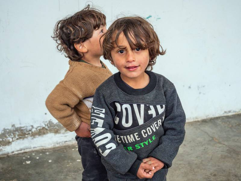 Hind Saleh Omar's children play outside the front of the half-built house that has become their home since being released from Al Hol camp under tribal agreements three months ago. Luke Pierce for The National