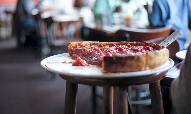 A partial deep dish pizza on a raised tray, with a serving spatula, in a restaurant.