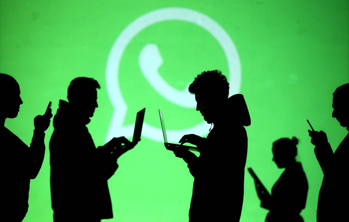 FILE PHOTO: Silhouettes of laptop and mobile device users are seen next to a screen projection of Whatsapp logo in this picture illustration taken March 28, 2018.  REUTERS/Dado Ruvic/Illustration/File Photo