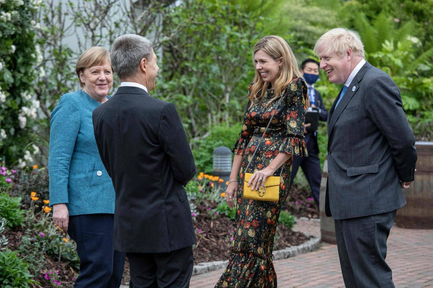 Germany's Chancellor Angela Merkel (L) and her husband, Joachim Sauer (2nd L) speak to Britain's Prime Minister Boris Johnson (R) and his wife Carrie Johnson at a reception with G7 leaders at The Eden Project in south west England on June 11, 2021. G7 leaders from Canada, France, Germany, Italy, Japan, the UK and the United States meet this weekend for the first time in nearly two years, for three-day talks in Carbis Bay, Cornwall. / AFP / POOL / Jack Hill