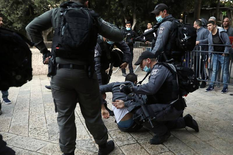 Israeli police officers detain a Palestinian man who tried to break through a security barrier to enter the the closed al-Aqsa mosque compound which remains shut to prevent the spread of coronavirus, in Jerusalem, Sunday, May 24, 2020. Muslims worldwide are marking a muted religious festival of Eid al-Fitr, the end of the fasting month of Ramadan. (AP Photo/Mahmoud Illean)