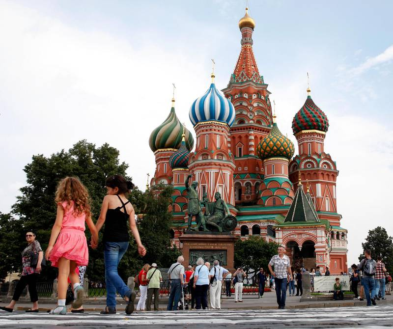 MOSCOW, RUSSIA - AUGUST 06:  Tourists explore Red Square in front of St. Basil's Cathedral ahead of the 14th IAAF World Athletics Championships on August 6, 2013 in Moscow, Russia.  (Photo by Jamie Squire/Getty Images)