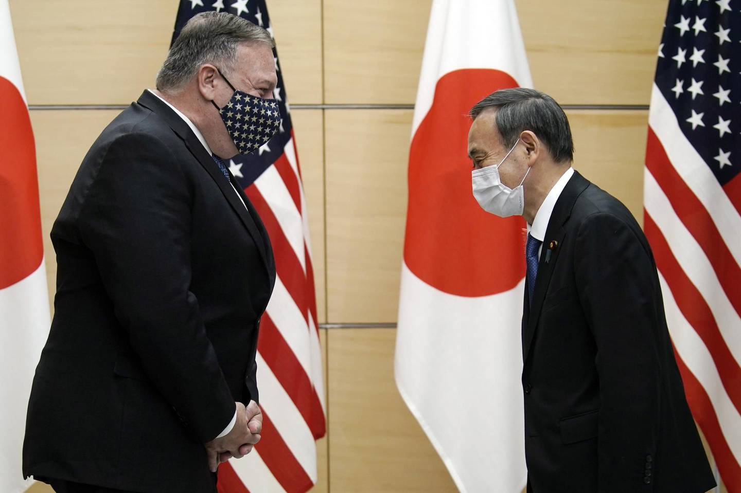 Michael Pompeo, U.S. Secretary of State, left, greets with Yoshihide Suga, Japan's prime minister, prior to a meeting at the prime minister's office in Tokyo, Japan, on Tuesday, Oct. 6, 2020. Pompeowill attend the Quadrilateral Security Dialogue (Quad) ministerial meeting later Tuesday in a bid to keep up the pressure on China amid the coronavirus crisis rocking Washington. Photographer: Eugene Hoshiko/AP Photo/Bloomberg
