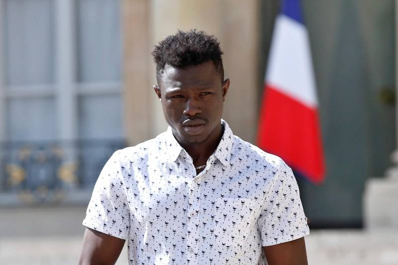 epa06768273 Mamoudou Gassama from Mali leaves the presidential Elysee Palace after his meeting with French President Emmanuel Macron in Paris, France, 28 May 2018. The 22 year old migrant Mamoudou Gassama, who is living in France illegally, is being honored by Macron for scaling an apartment building over the weekend to save a 4-year-old child dangling from a fifth-floor balcony.  EPA/THIBAULT CAMUS / POOL MAXPPP OUT