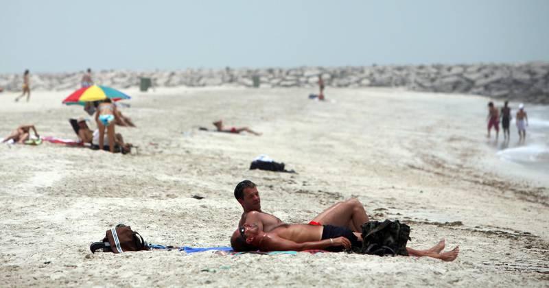 June 10, 2008 / Abu Dhabi /  Sun bathers relx on Ras Al Akhdar Beach in Abu Dhabi June 11, 2008. (Sammy Dallal / The National) *** Local Caption ***  sd-sunbather2.jpgsd-sunbather2.jpg