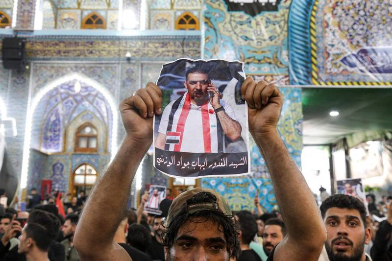 A mourner holds up a poster showing assassinated Iraqi anti-government activist Ihab al-Wazni (Ehab al-Ouazni) during his funeral at the Imam Hussein Shrine in the central holy shrine city of Karbala on May 9, 2021. Wazni, a coordinator of protests in the Shiite shrine city of Karbala, was a vocal opponent of corruption, the stranglehold of Tehran-linked armed groups and Iran's influence in Iraq. He was shot overnight outside his home by men on motorbikes, in an ambush caught on surveillance cameras. He had narrowly escaped death in December 2019, when men on motorbikes used silenced weapons to kill fellow activist Fahem al-Tai as he was dropping him home in Karbala, where pro-Tehran armed groups are legion. / AFP / Mohammed SAWAF
