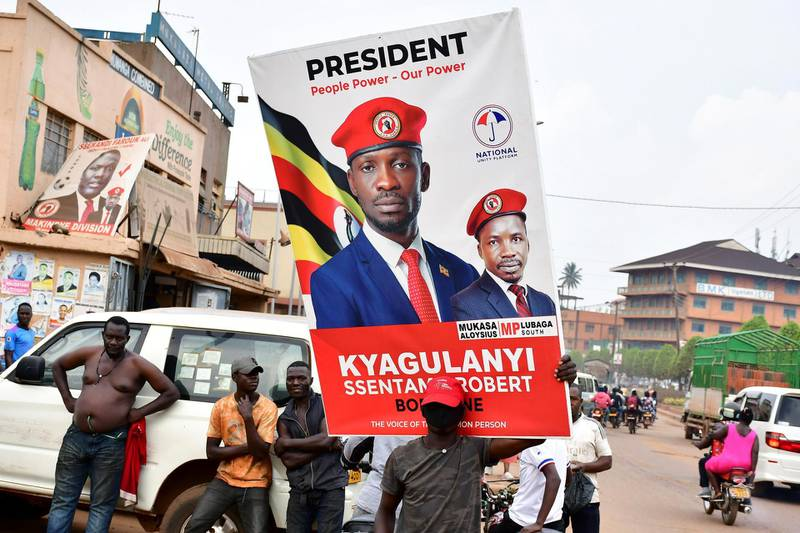 A supporter of Ugandan opposition Presidential candidate Robert Kyagulanyi also known as Bobi Wine carry his electoral campaign poster ahead of the presidential and parliamentary elections, in Kampala, Uganda January 12, 2021. REUTERS/Abubaker Lubowa