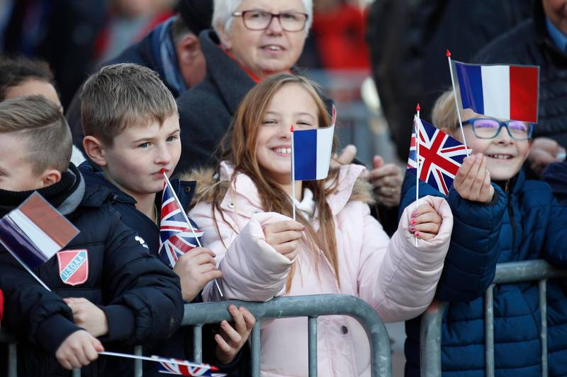 Children wave French and British flags before British Prime Minister Theresa May's arrival in Albert, northern France, Friday, Nov. 9, 2018. French President Emmanuel Macron will later welcome Theresa May and pay respects to the French and British soldiers killed during WWI at the Thiepval war cemetery. (AP Photo/Francois Mori)