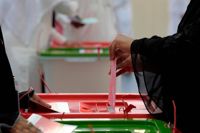 A Bahraini voter casts her ballot at a polling station in the Bahraini city of Al-Muharraq, north of Manama on November 24, 2018, as they wait to cast their vote in the parliamentary election. The polls opened at 8am local time (0500 GMT) and are set to close at 8pm. More than 350,000 Bahrainis are eligible to vote in Saturday's poll, according to justice minister Sheikh Khalid bin Ali al-Khalifa, adding that there were 54 polling stations across the country.   / AFP / STR